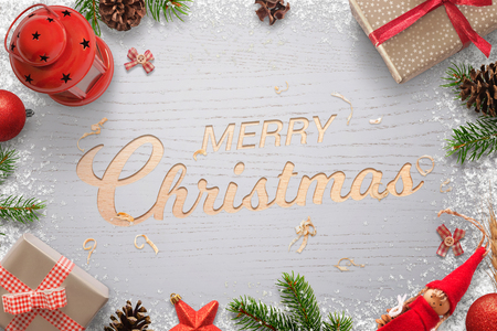 Merry christmas text carved in a wooden surface and surrounded