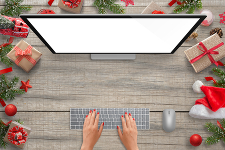 Work on computer with isolated screen for mockup presentation. Christmas scene with decorations. Woman typing on keyboard. Top view.