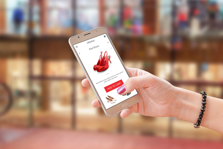 Online shoping with commerce app or web site. Woman holding modern smart phone. Shopping center in background. Фото со стока
