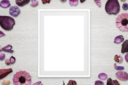 Picture frame with isolated white space for picture or text. Flower decorations around the frame. White wooden desk in background. Top view. Stock Photo
