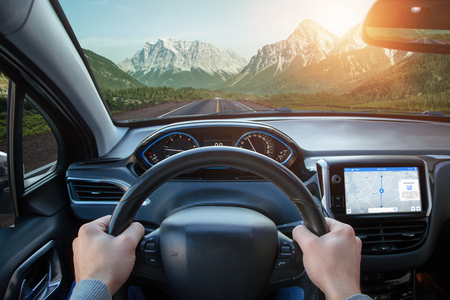 Relaxing car ride through mountainous areas. A view from the drivers angle to car interior and road. Stock Photo