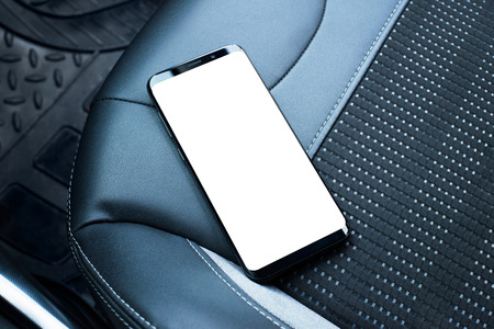 Mobile phone on the leather seat of a car. Isolated screen for app or web site mockup promotion.