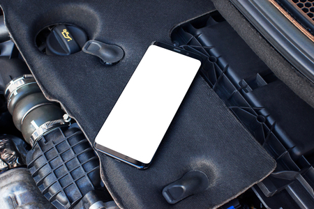 Mobile phone with isolated screen on car engine. Designed to promote apps for car servicing and analysis. Stock Photo