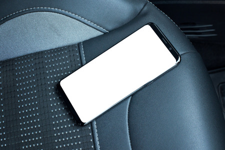 Mobile phone on car seat. Isolated screen for mockup. Black leather seat in background.