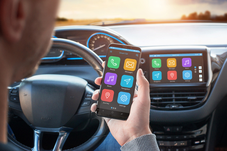 Driver uses a mobile phone with smart driving assistance apps. The app is connected to a car computer and is displayed on the board display. Stock Photo
