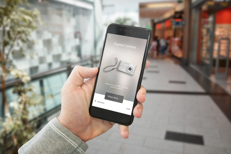 Shopping technological products with web site on smart phone display. Shopping mall in background. Фото со стока