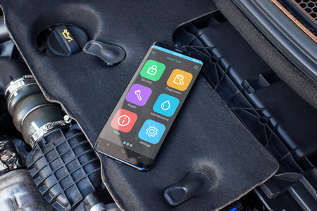 Mobile phone on a car engine with apps for diagnosing car problems.