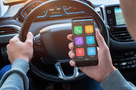 ドライバーは、必要な位置情報を見つけるためにスマートフォンを使用しています。ボードナビゲーションディスプレイを備えたモダンな車のイン