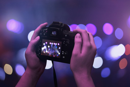 Camera in hands. Bokeh and concert, live music lights in background.
