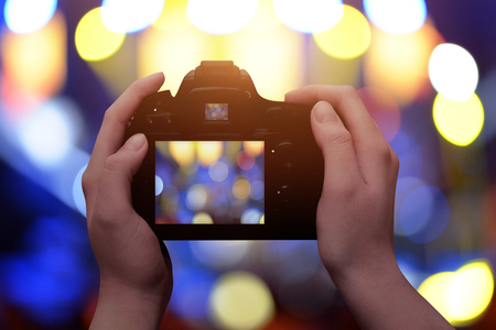Profesional digital camera in hands. Blue and yellow bokeh in background.