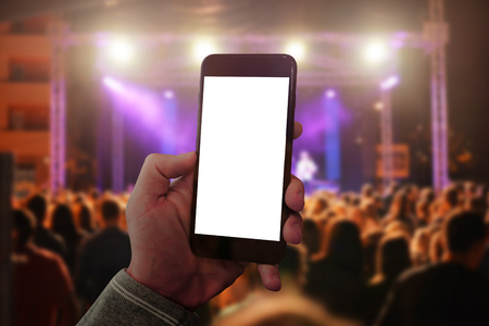 Man hand holding mobile smart phone and taking photo or video. Concert crowd and lights in background. Stock Photo