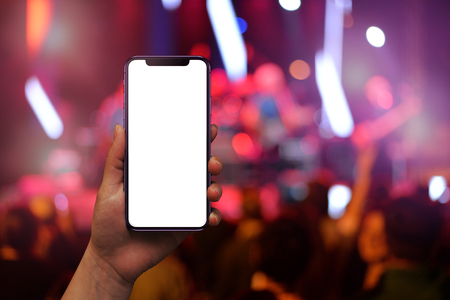 Modern mobile phone in woman hand with isolated screen for mockup. Live music concert and crowd in background. Stock fotó