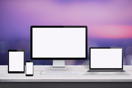 Responsive web design mockup. Devices with isolated screen on white wooden desk. Purple background. Stock Photo