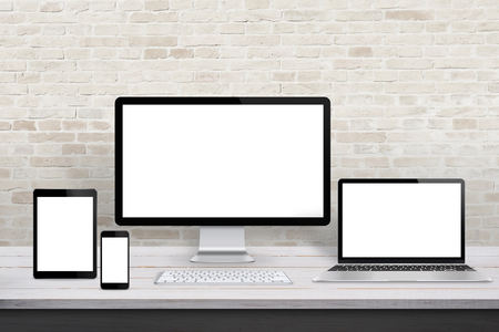 Multiple display devices for responsive web desing promotion. Modern office desk with brick wall in background.
