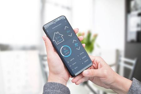 La mujer usa una aplicación móvil moderna con una interfaz de diseño plano moderno para controlar la seguridad del hogar; iluminación y temperatura del aire. Foto de archivo