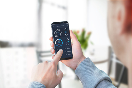 Guy use smart home control app to control lighting in living room interior. Archivio Fotografico