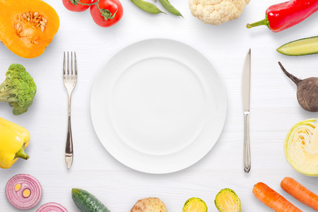 Empty plate fork and knife surrounded with vegetables. Flat lay, close up. Stock Photo