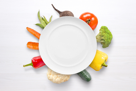 Empty plate with vegetables in background on white wooden surface. Фото со стока