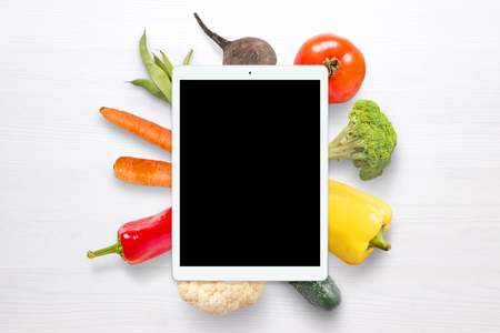 Blank tablet for mockup. Vegetables in background on white wooden table.