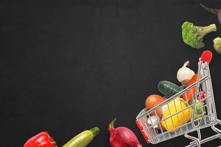 Fresh vegan cuisine ingridients and city market cart on dark surface. Stok Fotoğraf