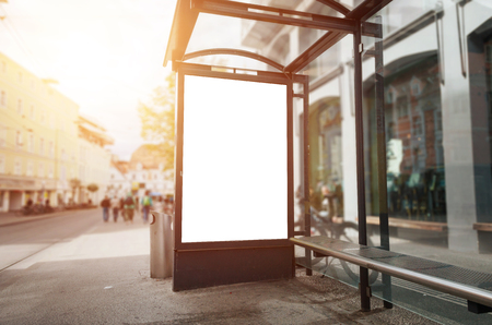 Bus stop billboard mockup. Sun light and street in background. Фото со стока
