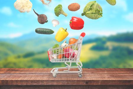 Gemüse fallen in Marktwagen auf Holztisch. Landschaft im Hintergrund.