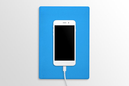 Phone connected to the charger on desk. Blue folder in background. Top view. Blank screen for mockup.
