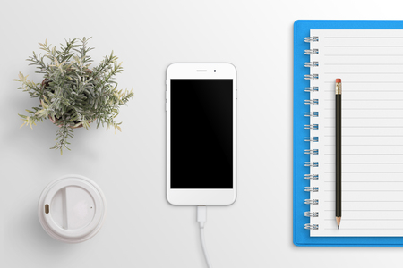 Phone mockup on white office desk surrounded with office supplies. Phone connected on charger. Flat lay.