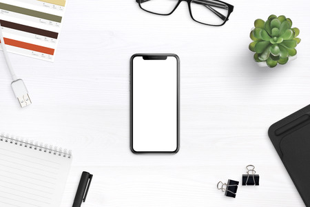 Modern smartphone mockup on a desk surrounded by supplies. Isolated round screen for app or web site promotion mockup. Foto de archivo