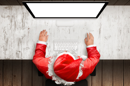 Santa claus work on desk computer with isolated display for mockup. Top view scene. Free space for text.