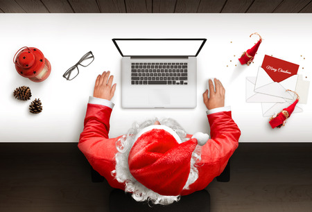 Santa Claus uses a laptop with isolated, blank screen for mockup, web site presentation. Top view Christmas composition.