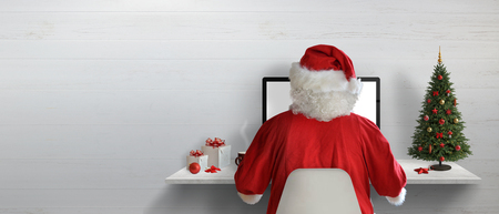 Santa Claus working on a computer in his office during Christmas holidays. Empty space on wall for text. Stock Photo