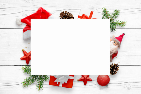 New Years scene with free space for greeting text on white paper and Christmas decorations in background. White wooden table in background.