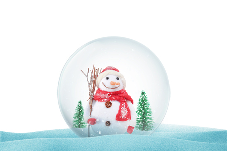 Isolated Christmas magic ball on snow with snowman and trees. Christmas decorative ball with snow falling.