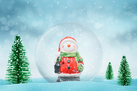 Christmas magic snow ball with Snowman. Snow falls in background. Christmas trees beside.