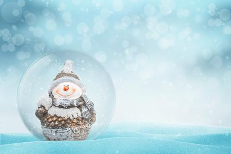 Año nuevo, bola mágica de Navidad con muñeco de nieve. Copie el espacio al lado. Luz y bokeh de fondo. Foto de archivo