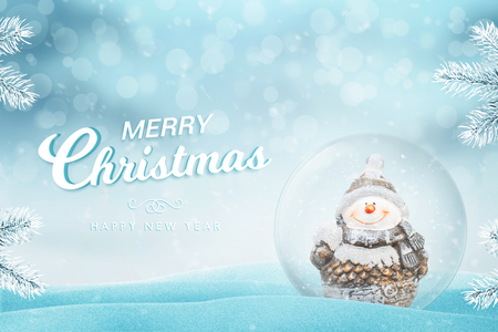 Christmas greeting card with text. Glass magic ball with snow and snowman beside.