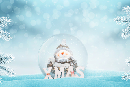 Crystal magic ball with a snowman. XMAS letters beside. Copy space above. Light and bokeh in background.