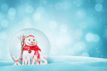 Snowman in New Year magic glass ball. XMAS letters beside. Free space on right side fot text. Bokeh in background. Stock Photo