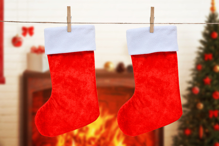 Christmas empty red socks hung on the rope. Fireplace, decorations and tree in background. 版權商用圖片 - 119207927