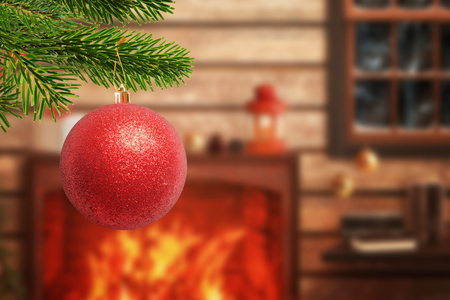 Christmas tree with decorative red ball in the foreground. Fireplace with gifts and Christmas decorations in background. Warm home atmosphere during the holidays.