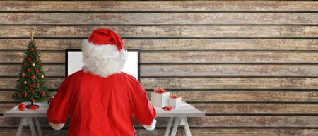 Santa Claus send greeting cards online. Copy space beside on wooden wall.