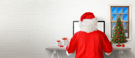 Santa work on a computer in his room. White brick wall in background with a free text space. Stockfoto