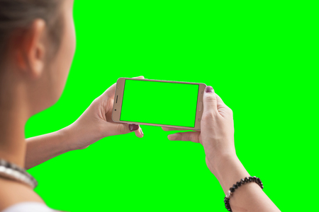 Girl watching a video or play game on a mobile phone. Chroma key isolated.