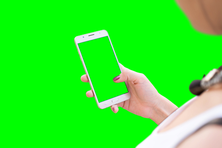 Girl work on smart phone. Isolated in green. Mockup for video editors. Stock Photo