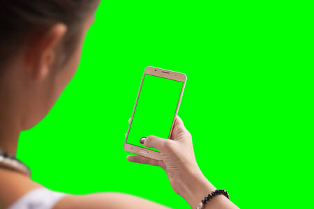 Girl use smart phone. Isolated screen and background in green for mockup.