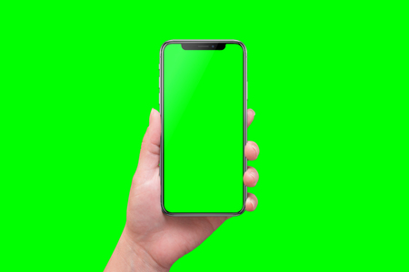Modern smart phone in hand close-up. Isolated screen and background in green. 写真素材