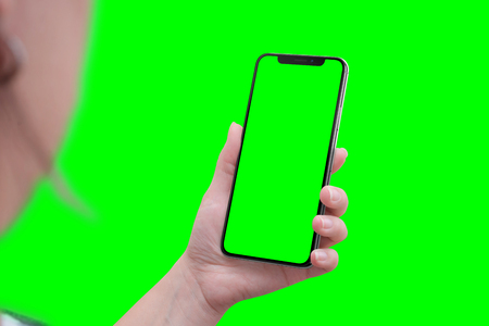 Modern smart phone with round edges in hand. Close-up. Isoalted screen and background in green, chroma key. Archivio Fotografico