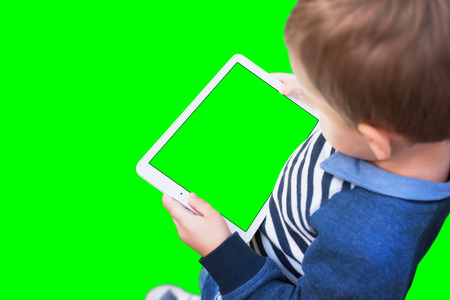 Boy play game on white tablet. Isolated screen and background in green, chroma key.
