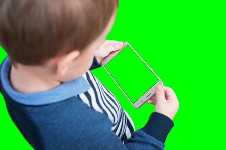 Kid holding smart phone in horizontal position. Isolated screen and background in green, chroma key. Stock Photo